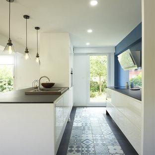 パリの広いエクレクティックスタイルのおしゃれなキッチン (シングルシンク、白いキャビネット、ラミネートカウンター、ガラスタイルのキッチンパネル、パネルと同色の調理設備、セラミックタイルの床、マルチカラーの床、黒いキッチンカウンター) の写真