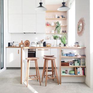 Exemple d'une petit cuisine parallèle tendance avec un placard à porte plane, des portes de placard blanches, un plan de travail en bois, une crédence blanche, un électroménager encastrable, une péninsule, un sol gris et un plan de travail beige.