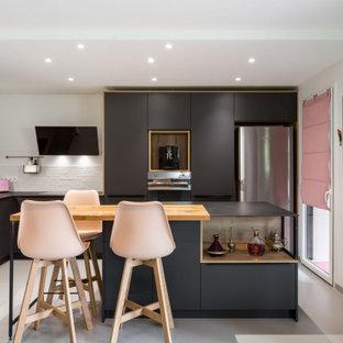 リヨンの中くらいのコンテンポラリースタイルのおしゃれなキッチン (シェーカースタイル扉のキャビネット、白いキッチンパネル、レンガのキッチンパネル、カラー調理設備、グレーの床、黒いキッチンカウンター) の写真