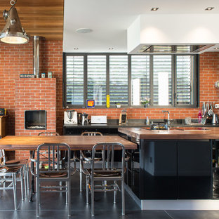 Cette photo montre une grand cuisine américaine parallèle industrielle avec un placard à porte plane, des portes de placard en bois sombre, un plan de travail en bois, une crédence rouge, un électroménager noir, béton au sol et un îlot central.