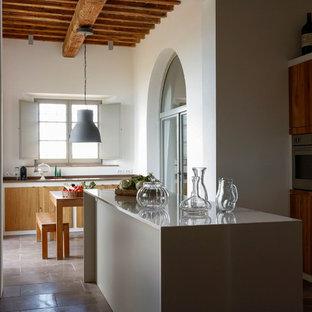 Immagine di una cucina mediterranea con ante lisce, ante in legno scuro, isola e pavimento marrone