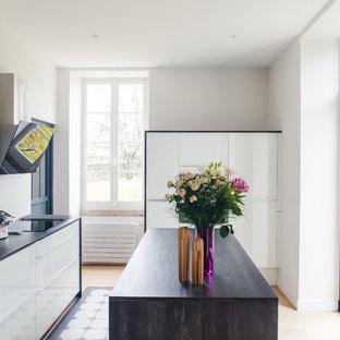 Idées déco pour une cuisine contemporaine en L fermée avec un évier posé, un placard à porte plane, des portes de placard blanches, une crédence blanche, un électroménager encastrable, un îlot central, un sol multicolore et un plan de travail marron.