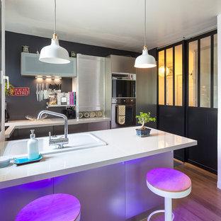 Inspiration pour une cuisine américaine design en U de taille moyenne avec une façade en inox, une crédence grise et une péninsule.