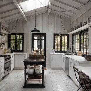 Foto di una grande cucina mediterranea con lavello da incasso, ante lisce, ante bianche, paraspruzzi grigio, paraspruzzi in legno, pavimento in legno verniciato, pavimento grigio e top bianco