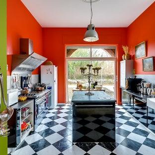 Idées déco pour une cuisine parallèle éclectique fermée et de taille moyenne avec un évier de ferme, un placard à porte plane, des portes de placard noires, un électroménager noir et un îlot central.