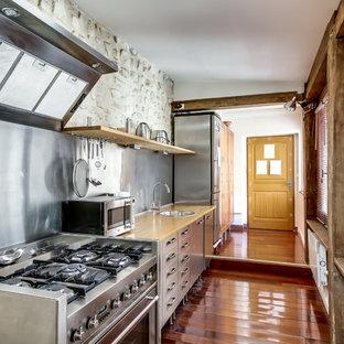 パリの大きいコンテンポラリースタイルのおしゃれなキッチン (ドロップインシンク、フラットパネル扉のキャビネット、ステンレスキャビネット、木材カウンター、メタリックのキッチンパネル、シルバーの調理設備、無垢フローリング、アイランドなし) の写真