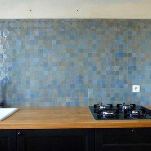 パリの大きいエクレクティックスタイルのおしゃれなキッチン (アンダーカウンターシンク、シェーカースタイル扉のキャビネット、黒いキャビネット、木材カウンター、青いキッチンパネル、テラコッタタイルのキッチンパネル、テラコッタタイルの床、アイランドなし、赤い床) の写真