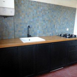 パリの広いエクレクティックスタイルのおしゃれなキッチン (アンダーカウンターシンク、シェーカースタイル扉のキャビネット、黒いキャビネット、木材カウンター、青いキッチンパネル、テラコッタタイルのキッチンパネル、テラコッタタイルの床、アイランドなし、赤い床) の写真