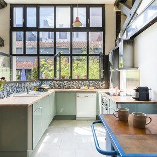 Cette image montre une cuisine urbaine en U avec un évier 2 bacs, un placard à porte plane, des portes de placards vertess, un plan de travail en bois, une crédence multicolore, un électroménager blanc, un sol blanc et un plan de travail beige.