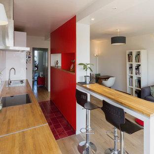 Idée de décoration pour une cuisine ouverte linéaire design de taille moyenne avec un îlot central.