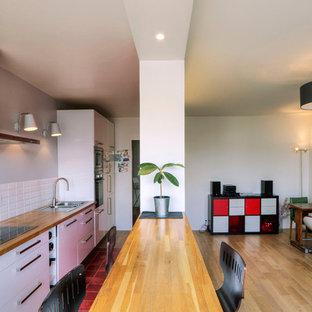 Cette photo montre une grande cuisine ouverte linéaire tendance avec un évier posé, un placard à porte plane, des portes de placard blanches, un plan de travail en bois, une crédence blanche, un sol en bois brun et une péninsule.