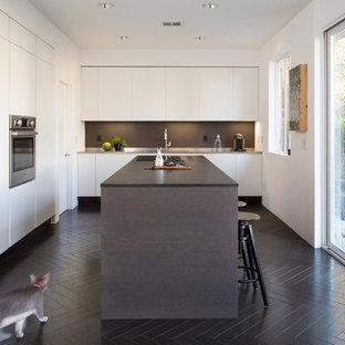 Cette photo montre une cuisine tendance en L avec un placard à porte plane, des portes de placard blanches, une crédence noire, un électroménager en acier inoxydable, un îlot central, un sol noir et un plan de travail noir.