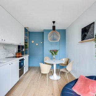 Idées déco pour une cuisine ouverte linéaire contemporaine avec un évier encastré, un placard à porte plane, des portes de placard blanches, une crédence blanche, une crédence en dalle de pierre, un électroménager en acier inoxydable, un sol en bois clair, aucun îlot et un sol beige.