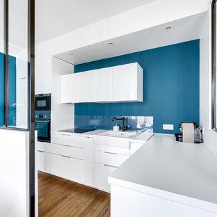 Aménagement d'une cuisine contemporaine en L avec un évier de ferme, un placard à porte plane, des portes de placard blanches, un sol en bois brun, aucun îlot, un sol marron et un plan de travail blanc.