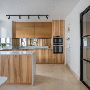 Inspiration pour une cuisine design en U avec un évier encastré, un placard à porte plane, des portes de placard en bois brun, un électroménager en acier inoxydable, une péninsule, un sol beige et un plan de travail blanc.
