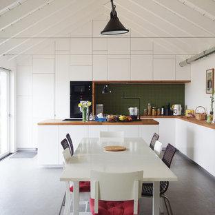 Réalisation d'une grande cuisine américaine design en L avec des portes de placard blanches, un plan de travail en bois, une crédence verte, une crédence en carreau de céramique, un électroménager noir, un sol en vinyl, un îlot central et un placard à porte plane.