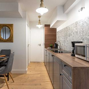 Aménagement d'une petite cuisine américaine linéaire classique avec un évier posé, un placard avec porte à panneau surélevé, des portes de placard grises, un plan de travail en bois, une crédence grise, aucun îlot, un sol beige et un plan de travail marron.
