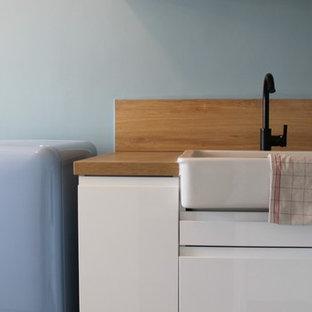 Foto di una cucina a L minimalista di medie dimensioni con ante lisce, ante bianche, top in laminato, paraspruzzi arancione, pavimento in cemento e top arancione