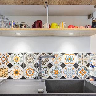 Свежая идея для дизайна: угловая кухня-гостиная среднего размера в классическом стиле с одинарной раковиной, светлыми деревянными фасадами, столешницей из ламината, оранжевым фартуком, фартуком из керамической плитки, техникой под мебельный фасад, полуостровом и черной столешницей - отличное фото интерьера
