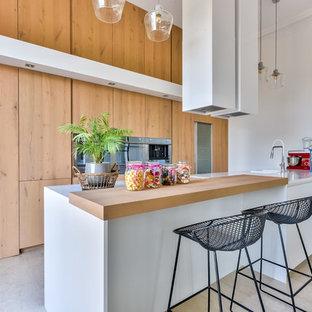 Cette image montre une grand cuisine design avec des portes de placard en bois clair, un plan de travail en surface solide, un plan de travail blanc, un évier 1 bac, un placard à porte plane, un électroménager en acier inoxydable, une péninsule et un sol gris.