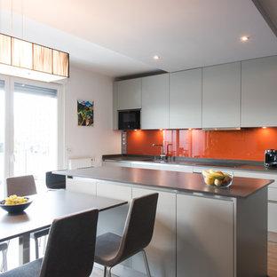 Ejemplo de cocina comedor lineal, actual, grande, con fregadero integrado, armarios con rebordes decorativos, puertas de armario grises, encimera de cuarcita, salpicadero naranja, salpicadero de vidrio templado, electrodomésticos con paneles, suelo de madera clara y una isla