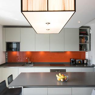 Cette photo montre une cuisine américaine parallèle tendance de taille moyenne avec une crédence orange, une crédence en feuille de verre, un îlot central, un évier encastré, un placard à porte plane, des portes de placard blanches et un électroménager encastrable.