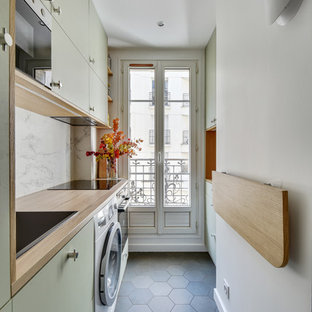 Inspiration for a contemporary single-wall separate kitchen in Paris with a drop-in sink, flat-panel cabinets, green cabinets, wood benchtops, white splashback, panelled appliances, cement tiles, no island, grey floor and beige benchtop.