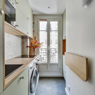 Inspiration pour une cuisine linéaire design fermée avec un évier posé, un placard à porte plane, des portes de placards vertess, un plan de travail en bois, une crédence blanche, un électroménager encastrable, un sol en carreaux de ciment, aucun îlot, un sol gris et un plan de travail beige.