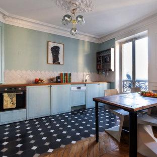パリのエクレクティックスタイルのおしゃれなキッチン (フラットパネル扉のキャビネット、青いキャビネット、木材カウンター、シルバーの調理設備、アイランドなし、黒い床、茶色いキッチンカウンター) の写真