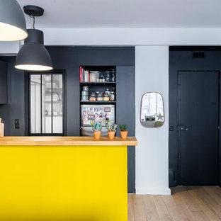 Kleine Moderne Wohnküche ohne Insel in L-Form mit Waschbecken, flächenbündigen Schrankfronten, grauen Schränken, Arbeitsplatte aus Holz, Rückwand aus Zementfliesen, Elektrogeräten mit Frontblende, Zementfliesen und schwarzem Boden in Paris