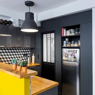 パリの小さいコンテンポラリースタイルのおしゃれなキッチン (シングルシンク、フラットパネル扉のキャビネット、グレーのキャビネット、木材カウンター、セメントタイルのキッチンパネル、セメントタイルの床、黒い床、マルチカラーのキッチンパネル、シルバーの調理設備、ベージュのキッチンカウンター) の写真