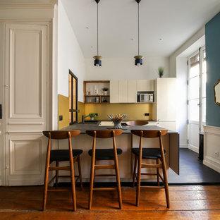 ボルドーの小さいエクレクティックスタイルのおしゃれなキッチン (シングルシンク、ベージュのキャビネット、ラミネートカウンター、黄色いキッチンパネル、黒い調理設備、ラミネートの床、黒い床、黒いキッチンカウンター) の写真