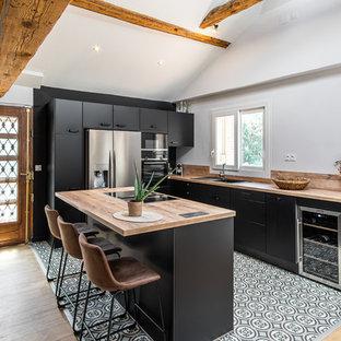 Aménagement d'une cuisine scandinave avec un placard à porte plane, des portes de placard noires, un plan de travail en bois, un électroménager en acier inoxydable, un îlot central et un sol multicolore.