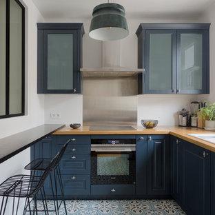 Geschlossene Moderne Küche in L-Form mit Triple-Waschtisch, profilierten Schrankfronten, blauen Schränken, Arbeitsplatte aus Holz, Küchenrückwand in Metallic, Rückwand aus Schiefer, schwarzen Elektrogeräten, buntem Boden und brauner Arbeitsplatte in Paris
