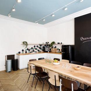 Cette photo montre une cuisine américaine scandinave en L avec un évier posé, un placard à porte plane, des portes de placard blanches, un plan de travail en bois, une crédence multicolore, un électroménager noir, un sol en bois clair, aucun îlot, un sol beige et un plan de travail beige.