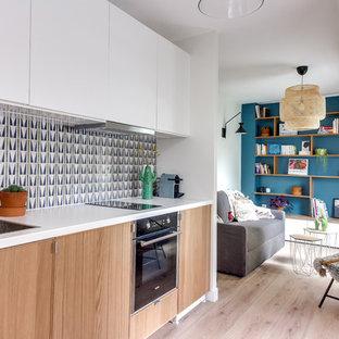 Exemple d'une cuisine ouverte linéaire tendance avec un évier posé, un placard à porte plane, des portes de placard en bois brun, une crédence multicolore, un électroménager en acier inoxydable, un sol en bois clair, aucun îlot et un sol beige.
