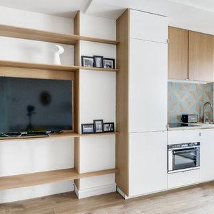 Foto de cocina lineal, escandinava, pequeña, abierta, sin isla, con encimera de madera, salpicadero azul, electrodomésticos con paneles, fregadero encastrado, puertas de armario blancas y suelo de madera clara