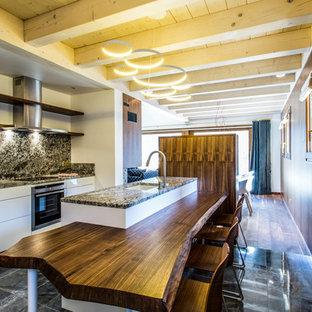 Modelo de cocina comedor lineal, contemporánea, de tamaño medio, con fregadero bajoencimera, puertas de armario blancas, salpicadero multicolor, electrodomésticos con paneles y una isla