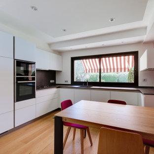 トゥールーズの中サイズのコンテンポラリースタイルのおしゃれなキッチン (一体型シンク、フラットパネル扉のキャビネット、グレーのキッチンパネル、シルバーの調理設備の、淡色無垢フローリング、黄色い床、グレーのキッチンカウンター) の写真
