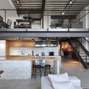 Idée de décoration pour une cuisine parallèle urbaine avec un placard à porte plane, des portes de placard en bois brun, un plan de travail en bois, une crédence grise, une crédence en brique, un électroménager en acier inoxydable, béton au sol, une péninsule et un sol gris.