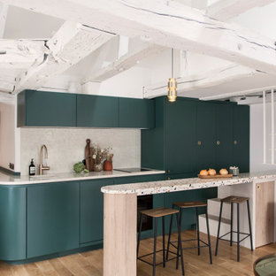 Inspiration for a contemporary galley kitchen in Paris with an undermount sink, flat-panel cabinets, green cabinets, beige splashback, panelled appliances, medium hardwood floors, a peninsula, brown floor and beige benchtop.