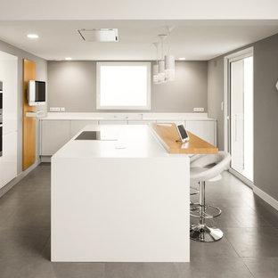 Cette photo montre une grand cuisine américaine linéaire tendance avec des portes de placard blanches et un îlot central.