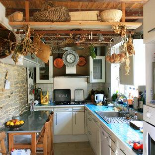 Ejemplo de cocina en L, bohemia, pequeña, cerrada, con fregadero encastrado, armarios con paneles lisos, puertas de armario blancas, encimera de azulejos, salpicadero blanco y electrodomésticos blancos