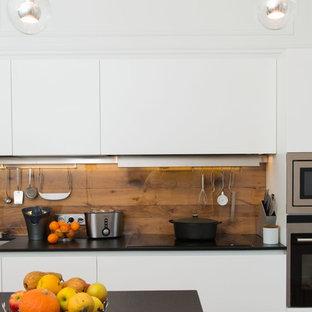 Cette photo montre une cuisine parallèle tendance de taille moyenne avec un placard à porte plane, des portes de placard blanches, une crédence marron, un électroménager en acier inoxydable et un îlot central.