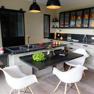 Cette photo montre une cuisine américaine industrielle en L de taille moyenne avec un évier 2 bacs, des portes de placard en bois clair et un îlot central.