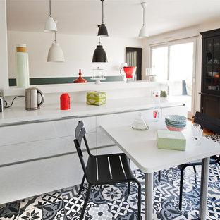 Idées déco pour une grande cuisine américaine parallèle contemporaine avec un évier intégré, un placard à porte affleurante, des portes de placard blanches, un plan de travail en surface solide, un sol en carreaux de ciment, un sol blanc et un plan de travail blanc.