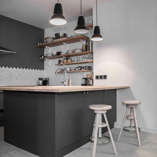 パリの中サイズのコンテンポラリースタイルのおしゃれなキッチン (アンダーカウンターシンク、インセット扉のキャビネット、黒いキャビネット、木材カウンター、グレーのキッチンパネル、大理石の床、シルバーの調理設備の、コンクリートの床、グレーの床、ベージュのキッチンカウンター) の写真