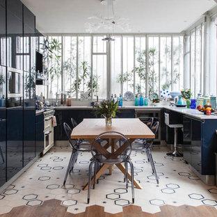 Cette photo montre une cuisine américaine tendance en U avec un placard à porte plane, des portes de placard bleues, un électroménager en acier inoxydable, un sol en carrelage de céramique, aucun îlot et un sol multicolore.