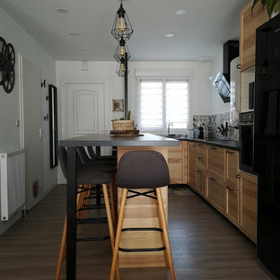 Mid-sized tropical l-shaped open plan kitchen in Bordeaux with a single-bowl sink, beaded inset cabinets, light wood cabinets, laminate benchtops, grey splashback, ceramic splashback, black appliances, laminate floors, with island, grey floor and black benchtop.