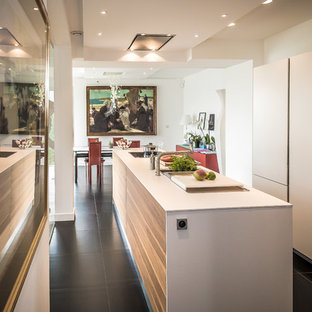 This is an example of a mid-sized contemporary single-wall eat-in kitchen in Brest with with island, an integrated sink, white cabinets, laminate benchtops, white benchtop, panelled appliances and black floor.